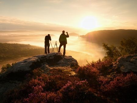 63823222 - photographers stay on cliff and takes photos. dreamy landscape fogy, misty orange sunrise in a beautiful valley below