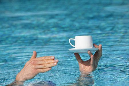54712535 - recommendation - best service - hand above water holding cup of coffee